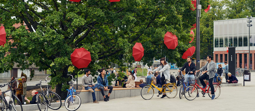 Students on Otaniemi campus. Open red umbrellas attached to trees, students sitting on a bench under the green-leaved trees. Photo by Aalto University /Unto Rautio