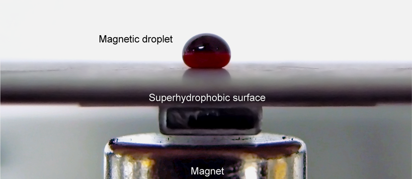 A ferrofluid droplet sitting on a measurement surface in the oscillating droplet tribometer measurement scheme. The magnet underneath the surface is also seen.