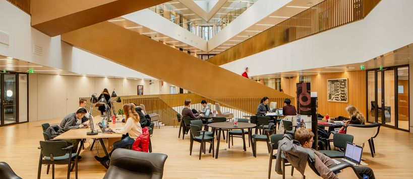 People studying in the School of Business main building with a large staircase in the background.