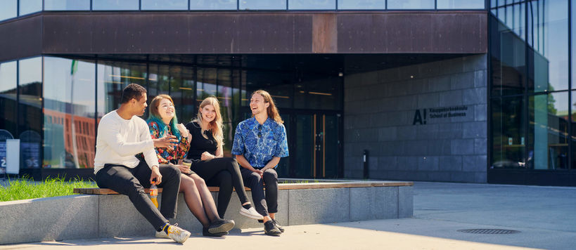Four students sitting outside the School of Business
