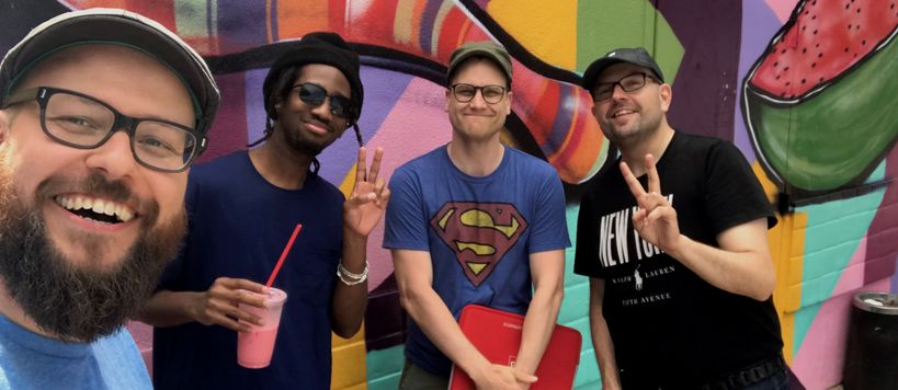 Four smiling men posing in front of a colorful graffiti wall.