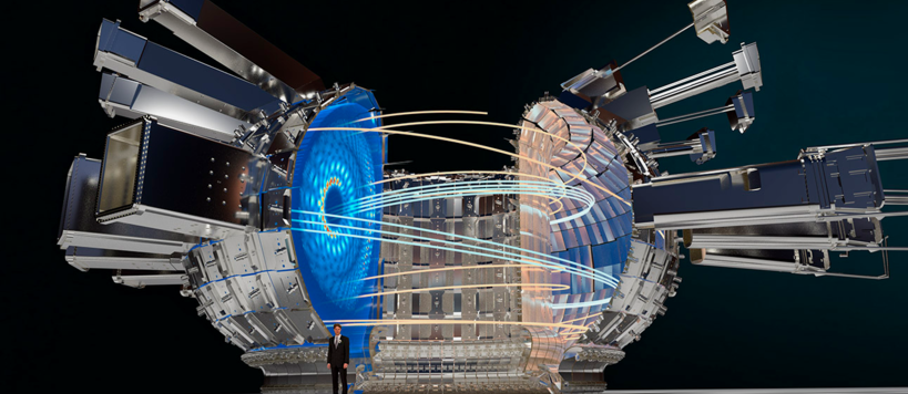 computer illustration of a cut away of the donut-shaped fusion reactor, showing that it much larger tha human