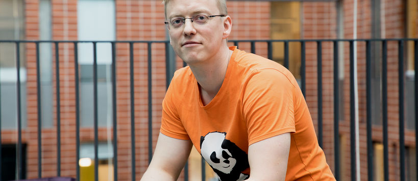 Jara Uitto sitting at Computer Science building, looking at the camera and wearing an orange t-shirt with a panda on it