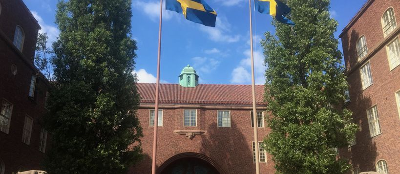 Swedish flags flying on KTH campus gates, building behind is of red brick