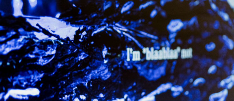 Detail of an artwork. Blue surface with blurry text.