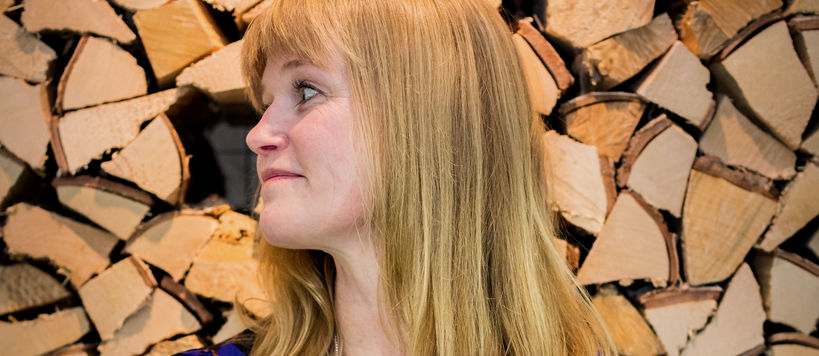 Anniina Suominen, an Associate Professor of Art Pedagogy at Aalto University's School of Arts, Design and Architecture. She is standing in front of the camera, smiling, arms crossed. In the background there is a stack of logs.