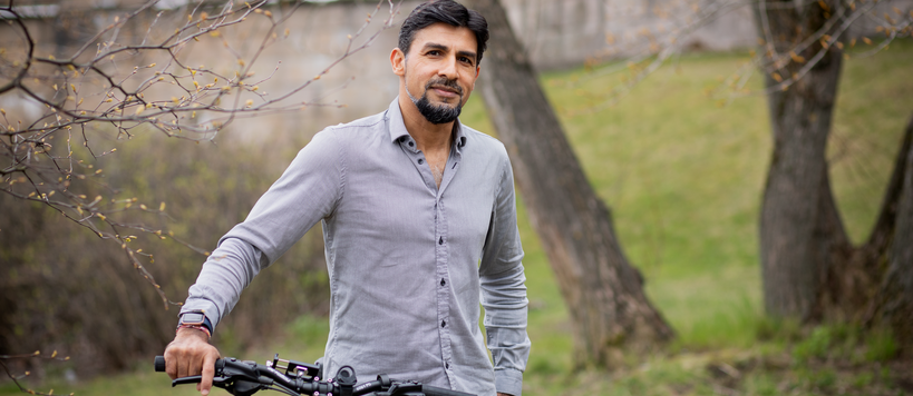 Nitin Sawhney standing outdoors with his bike, green grass and trees on the background