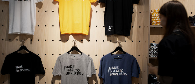 Colorful Made in Aalto University -t-shirts hanging at Aalto University Shop's wall