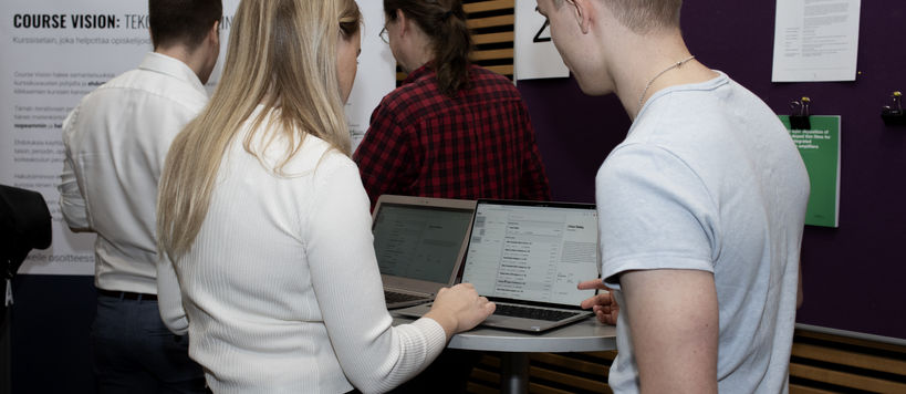 Young people looking some information together over a computer