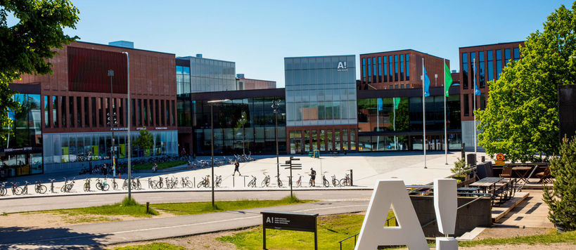 White Aalto logo with exclamation mark standing in the middle of Otaniemi campus in the summertime