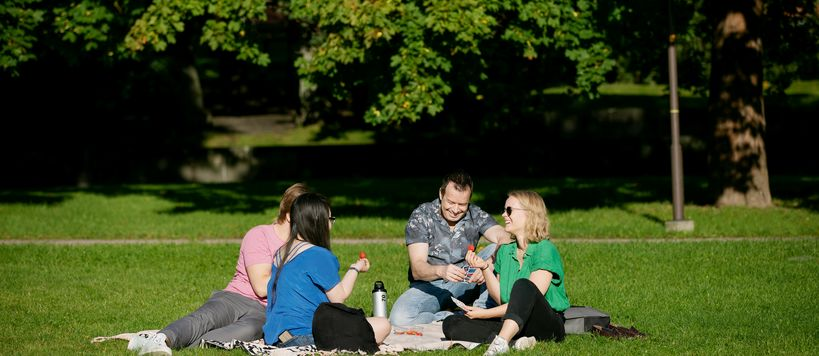 Students sitting in a park having a picnic