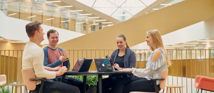 Four happy students in Aalto BIZ. Photo: Unto Rautio / Aalto University