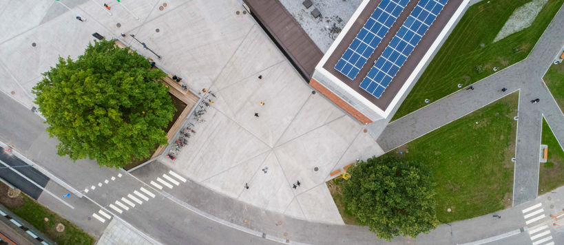 Aerial shot of the Korkeakoulunaukio square. There are solar panels on the Väre roof and trees on the square.