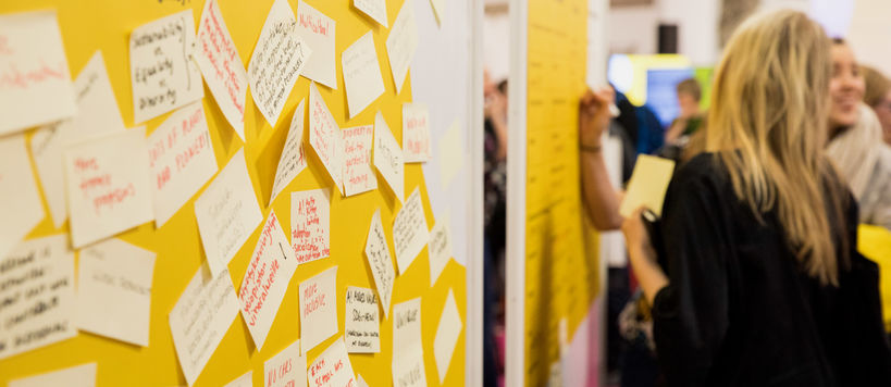 A yellow workshop wall with lots of sticky notes with text