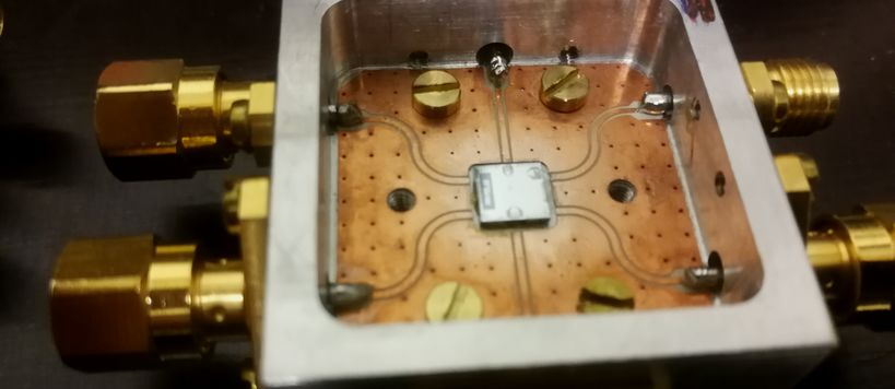 A small microchip containg quantum circuitry inside a metal sample holder