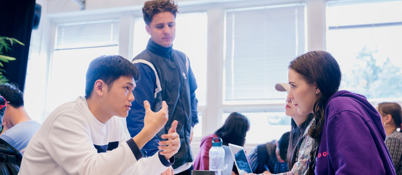 A group of four students discussing at a table. One is talking and making hand gestures and the others are listening intensely.