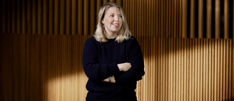 Johanna Fagerström pictured with her arms crossed in a blue knitted sweater. She is smiling and looking at something behind the photographer.
