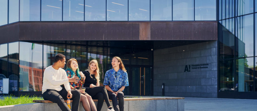 Four students sitting in on a wall outside the Aalto University School of Business building. They are all laughing and discussing vividly.