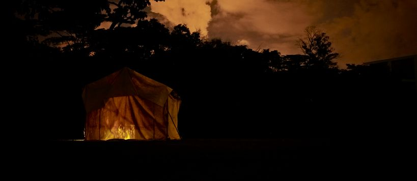 Still from the film Like Shadows Through Leaves, 2021. A lamp-lit tent stands in a dark landscape, it's orange interior matching the orange skyline