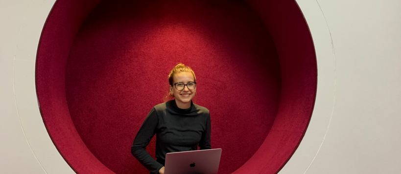 Svitlana Chaplinska sitting with her laptop and smiling towards the camera in a futuristic, round and red chair integrated to the wall at Aalto University campus.