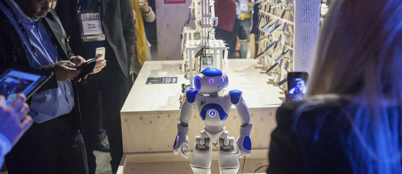 A small white and blue robot pictured on display at Aalto's monter at Slush