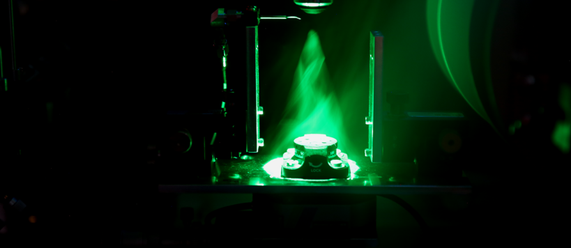A green laser light shining on a sample stage between two magnets