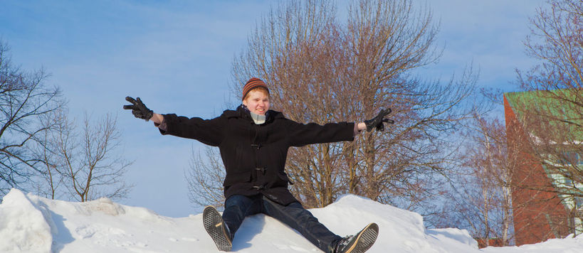 A happy student slides downhill a snowbank