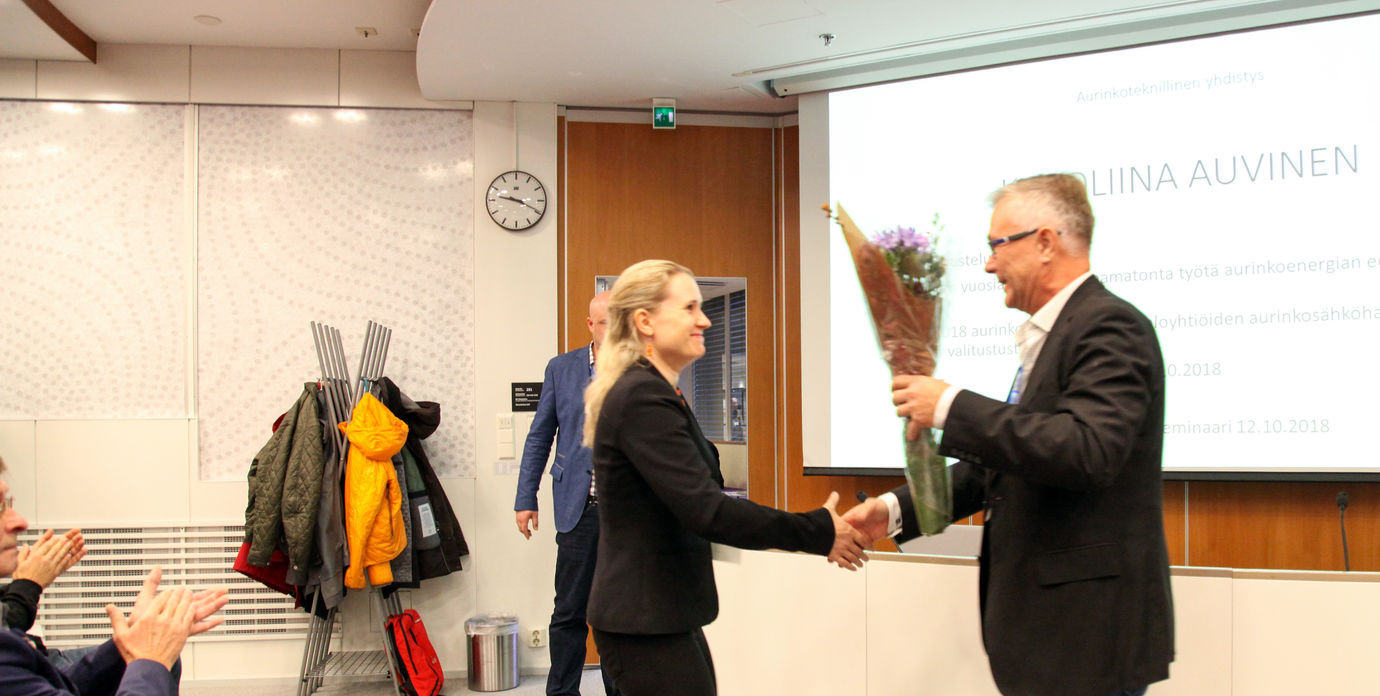 The photo shows Karoliina Auvinen receiving the annual solar award for 2018 from Christer Nyman. Photo: Mikko Arvinen / Sähköala.