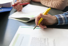 Two people with pens hovering over articles