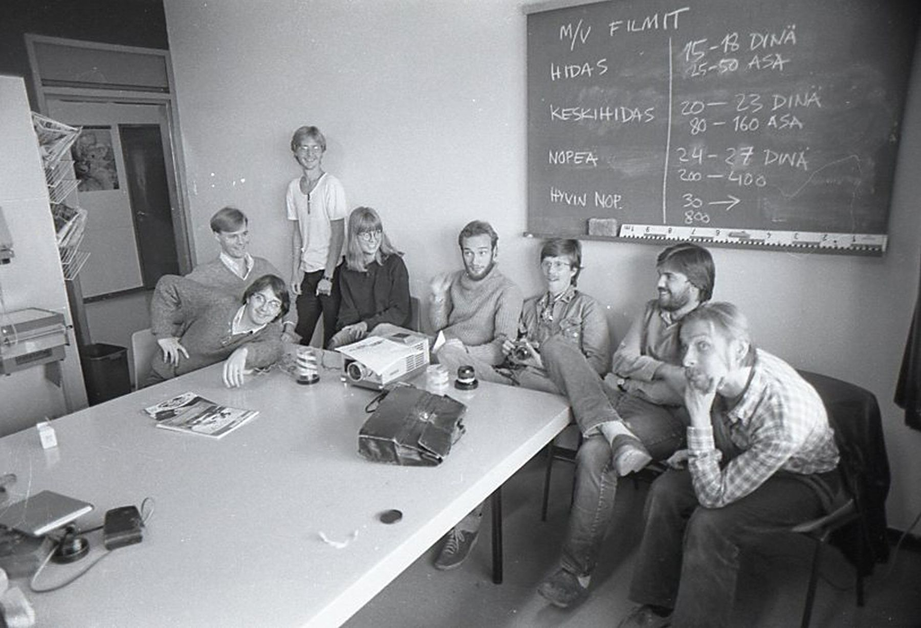 people posing at table in black and white