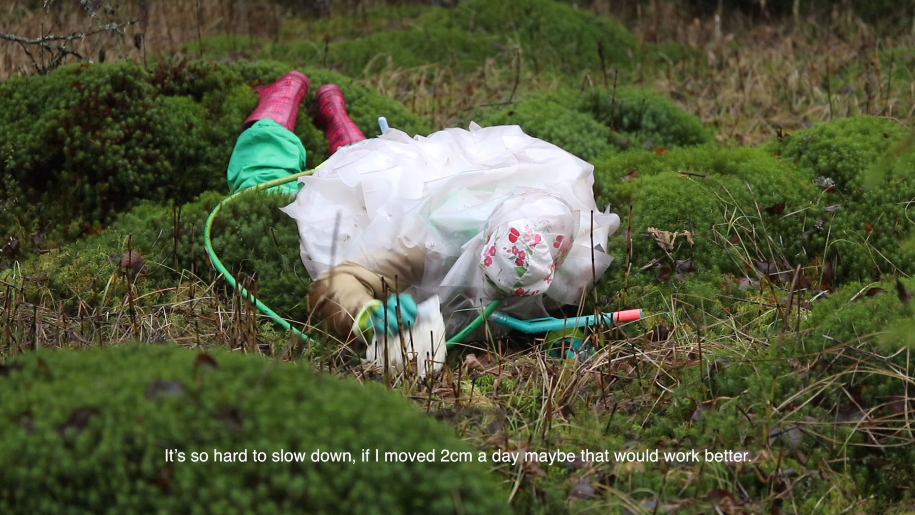 a person in a protective plastic suit lays on the ground in the woods exploring the bog and saying: 'It's so hard to slow down, if I moved 2cm a day maybe that would work better.