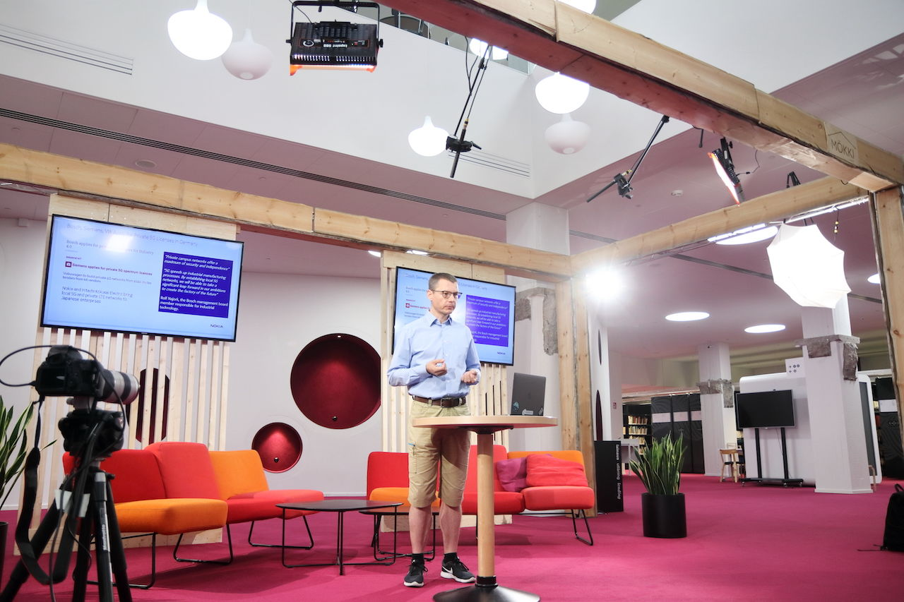 Man giving a lecture, standing in a large empty studio with colourful furniture.