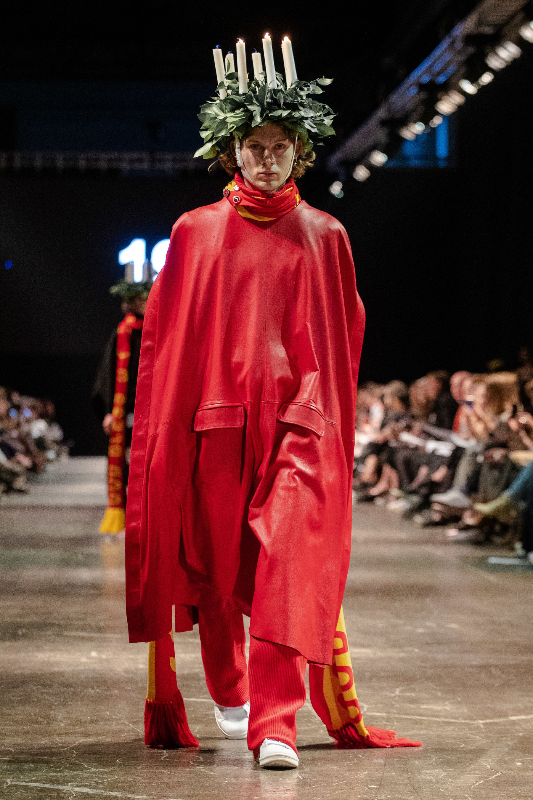 Model walking catwalk in red garment and headpiece with candles
