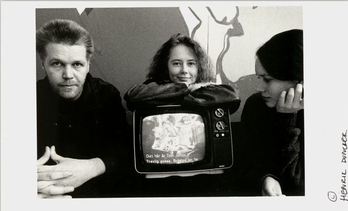 a man and two women posing with tv