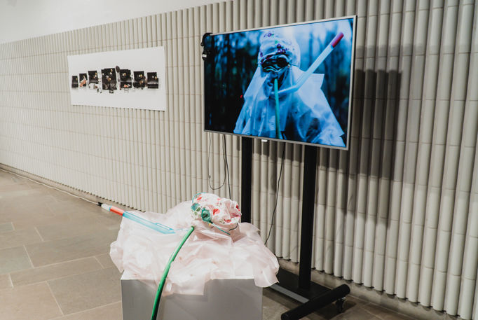 a photo from art exhibition Interspecies liminalities, 2019. A plastic suit, art video (&projector) and an art piece hanging on the wall.