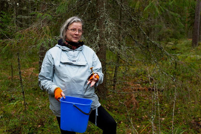 Professor Laura Beloff talks about mushrooms. She holds a blue bucket and a single mushroom.