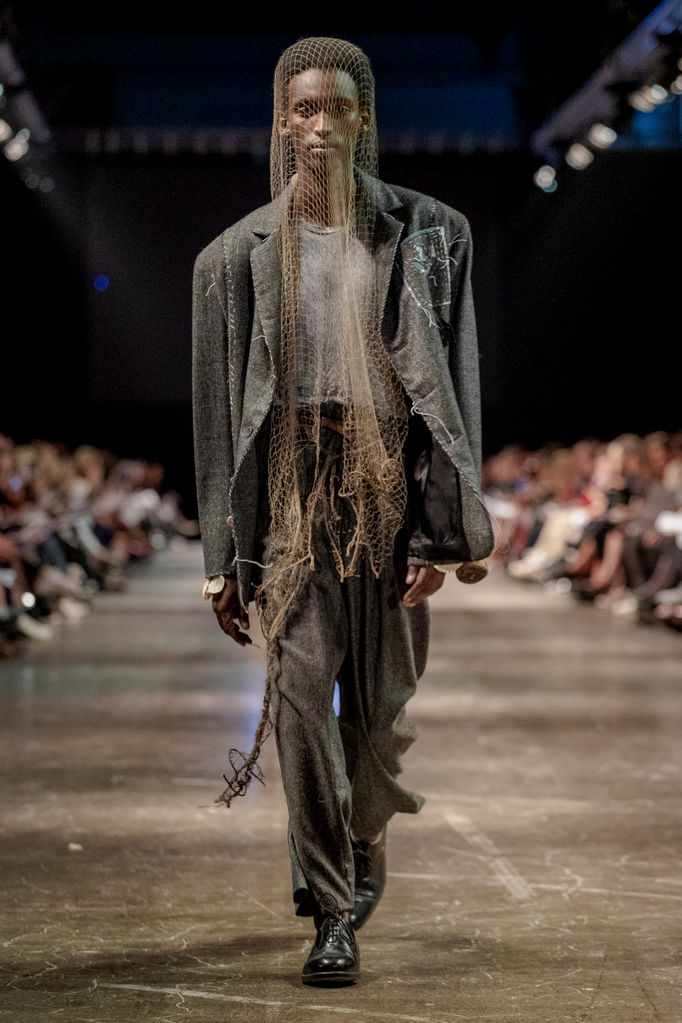Model walking down catwalk in garment with fishing net