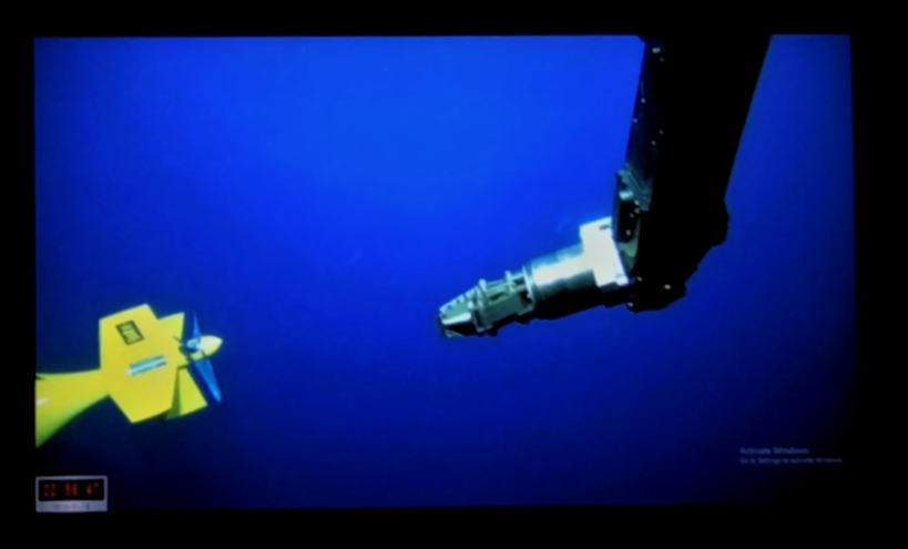 Remotely operated vessel reaches for AUV underwater