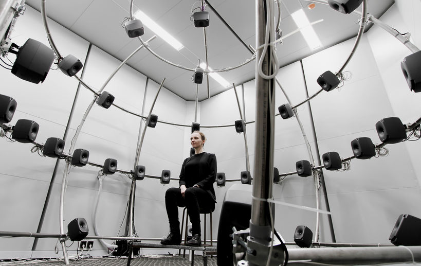 A person sitting at aalto acoustics lab's multichannel anechoic chamber photo benoit alary
