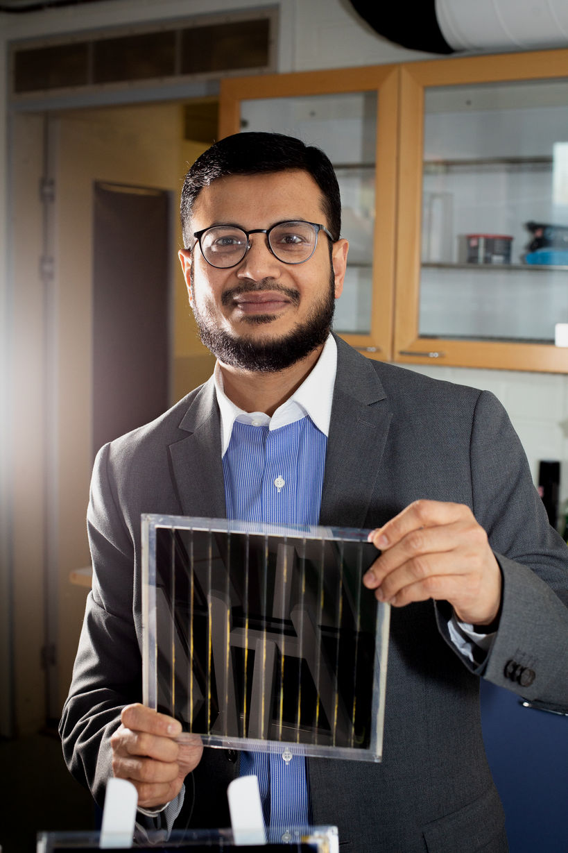 Dr Hashmi holding a printed solar panel