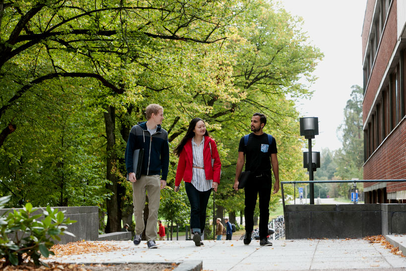 Three students in autumn walking on Aalto University campus, near Harald Herling Learning Centre.