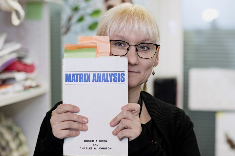 Professor Imonen holding a copy of a textbook up to the camera