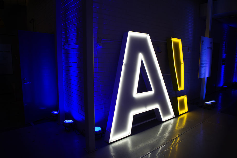 Human-sized lamp in the shape of the Aalto logo, capital A followed by an exclamation mark, stands in a dark space / photo by Aalto University, Lasse Lecklin