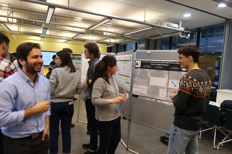 Students watching posters about machine learning.