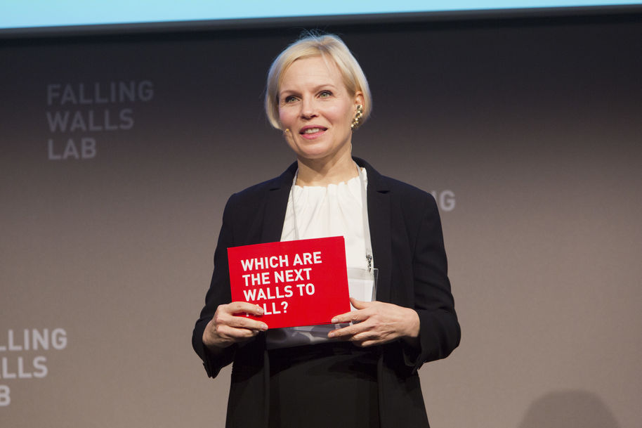 Falling Walls Founder on stage holding card