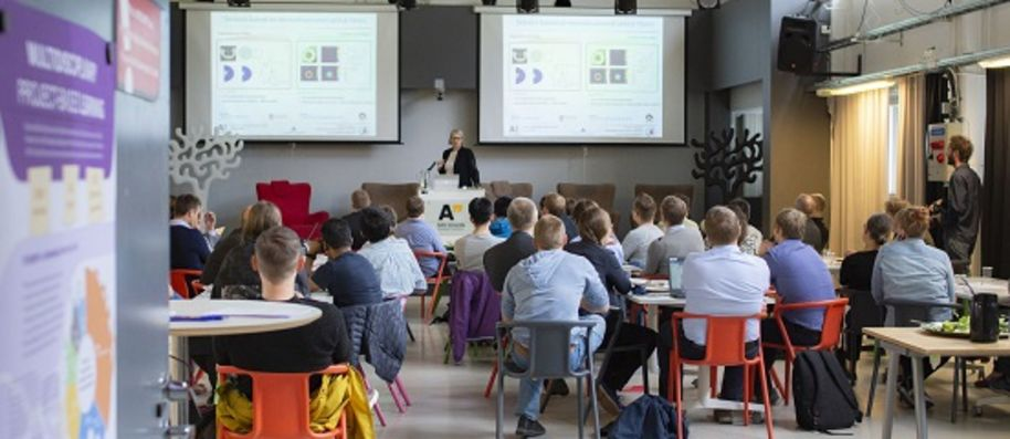 Audience listening to a presentation at the Aalto Sensors event in Aalto University Design Factory