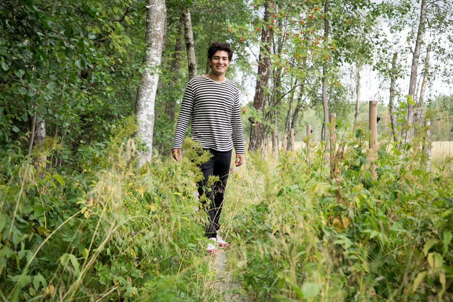 Ali Salloum walking at Laajalahti Nature Reserve in summer, surrounded by green bushes, trees and grass