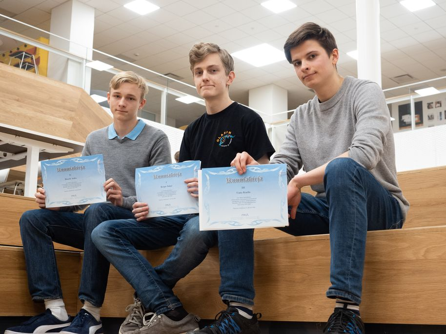 Henrik Aalto, Roope Salmi and Unto Karila sitting on the stairs and showing their certificates