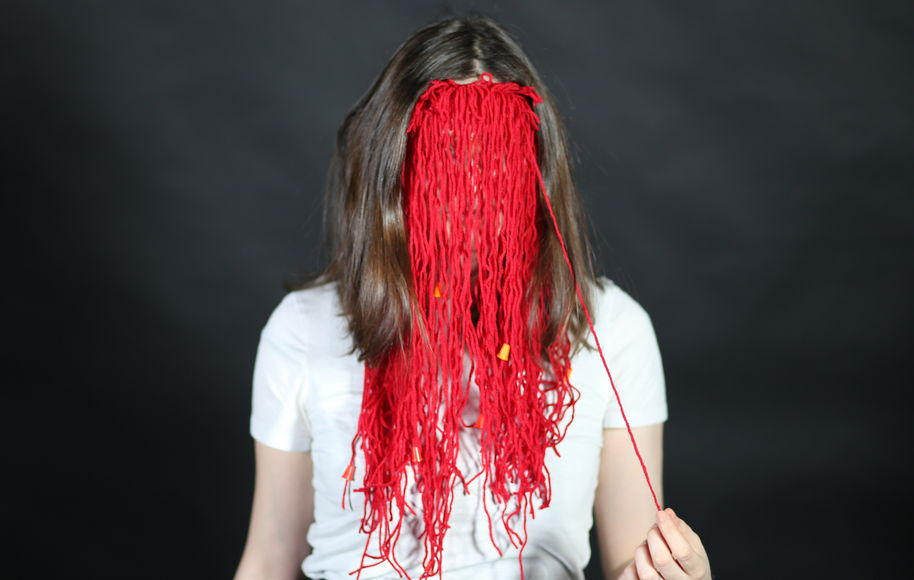 A person behind red mask made of yarn.