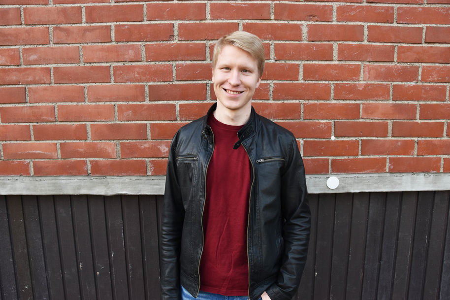 Aleksanteri smiling in front of the School of Chemical Engineering